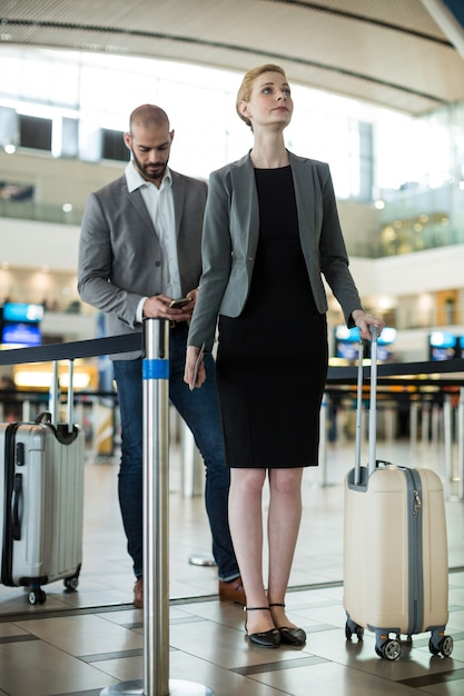 Businesspeople waiting in queue at a check-in counter with luggage Free Photo