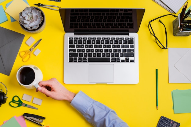 Businessperson holding cup of coffee and laptop over the yellow background Free Photo