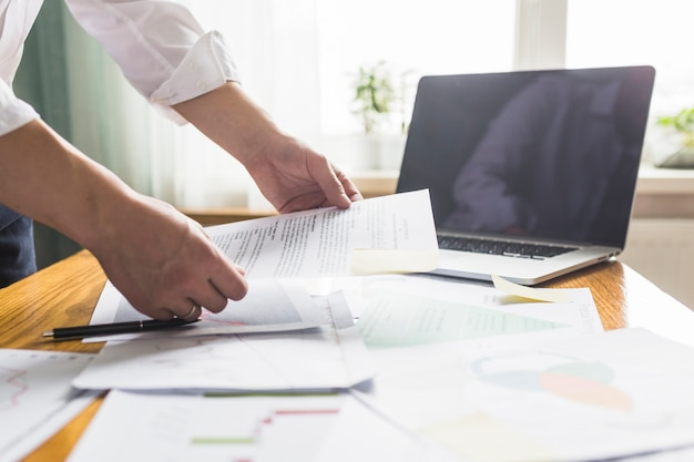 Businessperson's hand holding document over wooden desk Free Photo