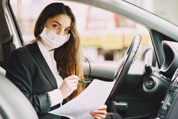 Businesswoman in a black mask sitting inside a car | Free Photo