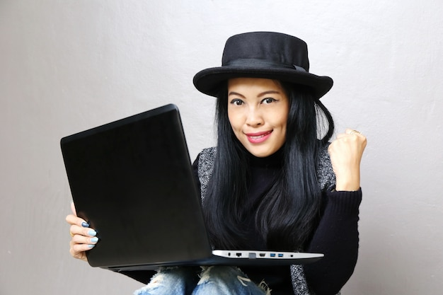 Businesswoman, charming beautiful tan skin asian business chic woman hand work on laptop and success  hand up Premium Photo