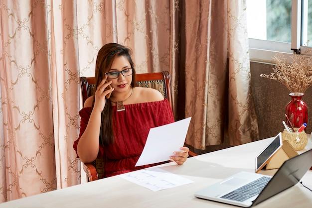 Businesswoman discussing document on phone Premium Photo