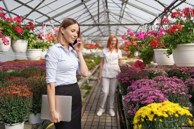電話で提案を話し合う実業家。彼女は花のある温室でラップトップを持っています。 無料写真