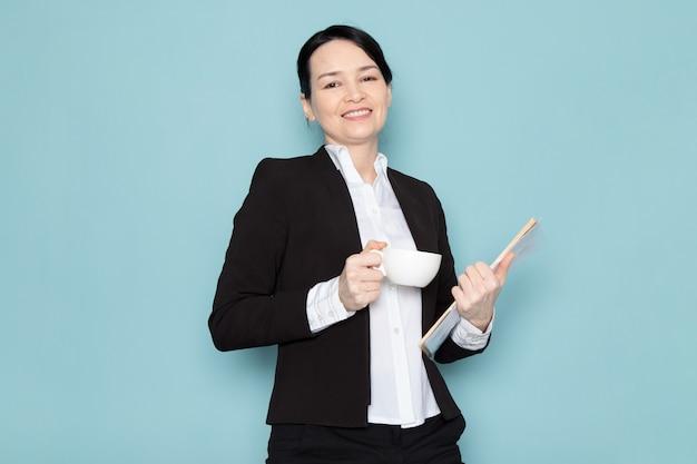 コーヒーを飲みながら雑誌を保持している実業家 無料写真