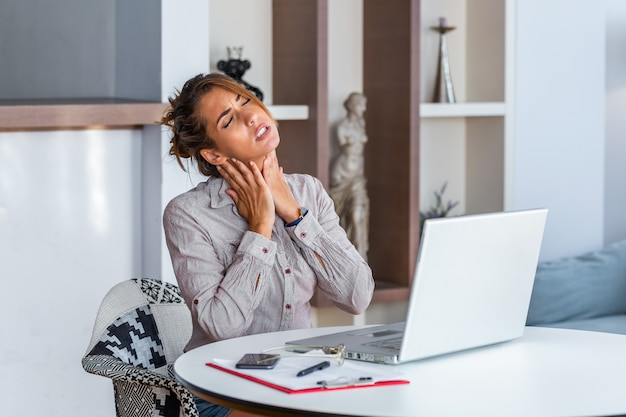 Businesswoman feeling pain in neck after sitting at the table with laptop. Premium Photo
