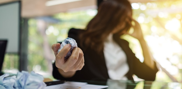 Businesswoman get stressed , screwed up papers while having a problem at work in office Premium Photo