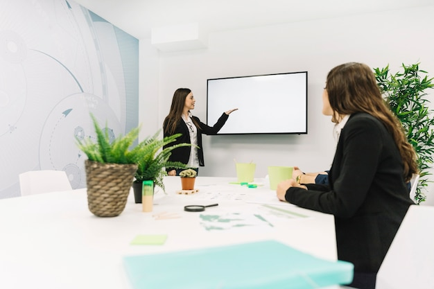 Businesswoman giving presentation to her colleague Free Photo