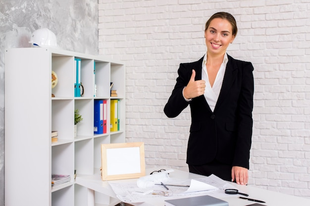 Businesswoman giving a thumbs up Free Photo