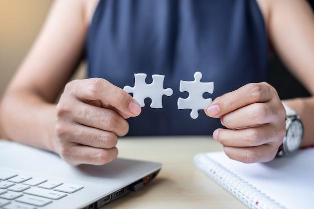 Businesswoman hand connecting couple puzzle piece Premium Photo