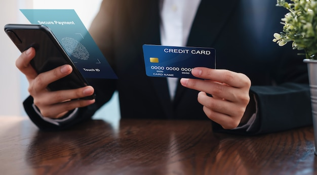 Businesswoman hand holding credit card and smartphone interface secure payment. Premium Photo