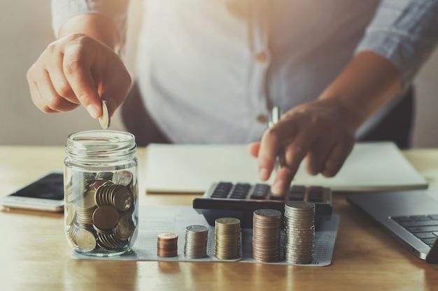 Businesswoman hand puting coins in glass for saving money Premium Photo