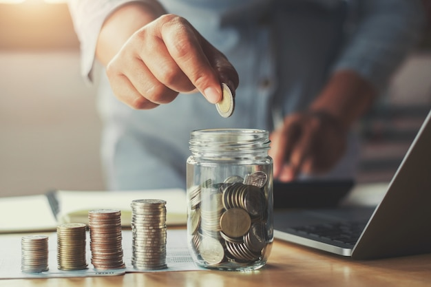 Businesswoman hand puting coins in glass for saving money Premium Photo