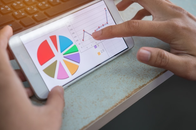 Businesswoman hands using data graph report in smartphone for checking analyze marketing f Premium Photo