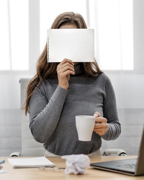 Деловая женщина, держащая пустой блокнот на лице Бесплатные Фотографии