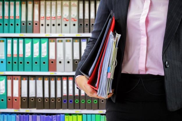 Businesswoman holding data files on binder shelves background Premium Photo