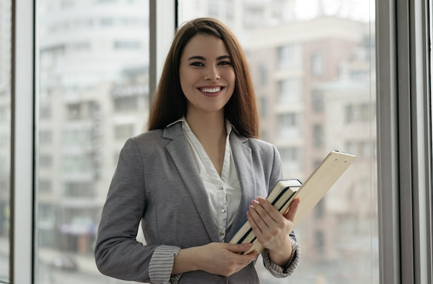 Businesswoman holding documents and books, standing in office near window Premium Photo