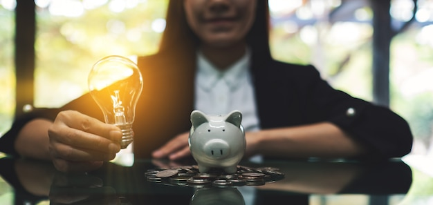 A businesswoman holding a light bulb next to a piggy bank on pile of coins on the table for saving money concept Premium Photo