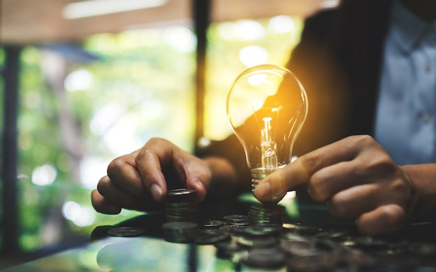 Businesswoman holding lightbulb while stacking coins on table for saving energy and money concept Pr