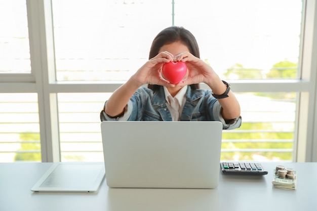 Businesswoman holding red heart symbol on table with computer Premium Photo