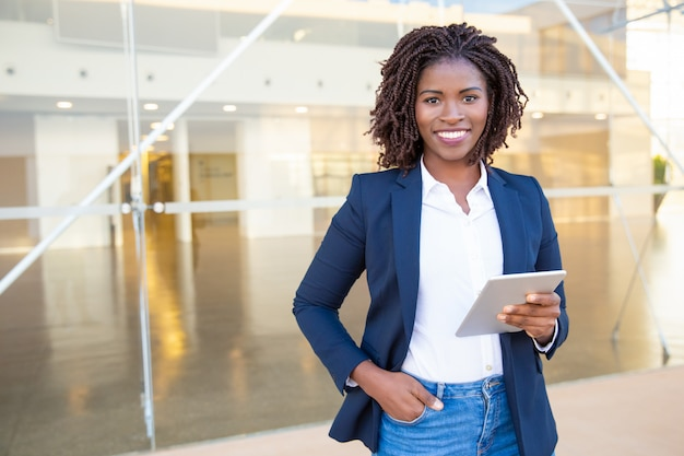 Businesswoman holding tablet pc and smiling at camera Free Photo