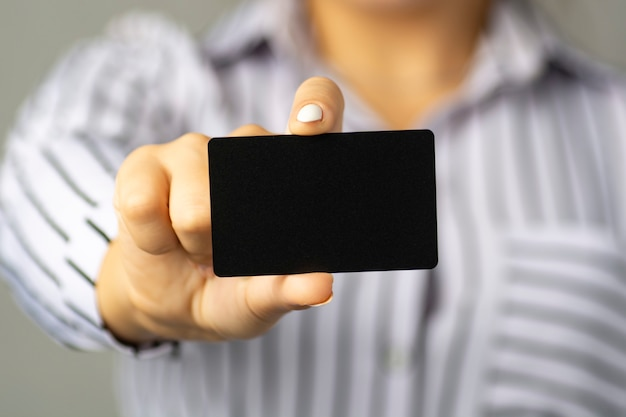 Деловая женщина держит в руке черную визитную карточку. Premium Фотографии