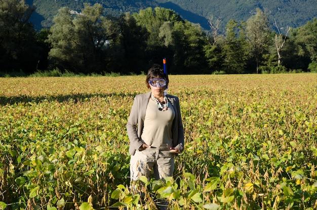 Деловая женщина в костюме, стоящая в поле с водолазной маской Бесплатные Фотографии