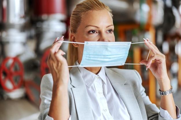 코로나 바이러스 동안 그녀의 공장에 서있는 동안 얼굴 마스크를 씌우고 소송에서 사업가. 프리미엄 사진