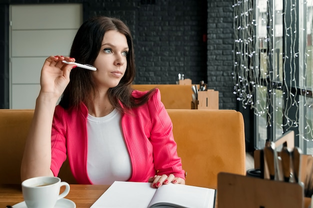 Businesswoman is sitting in a cafe thinking about something Premium Photo