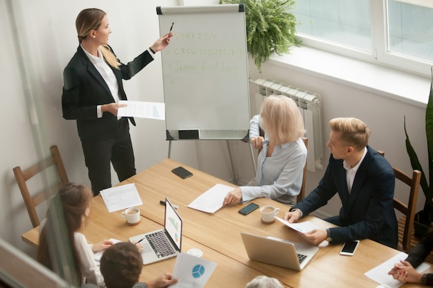 Businesswoman leader giving presentation explaining team goals at group meeting Free Photo