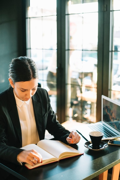 Businesswoman looking in diary over desk Free Photo