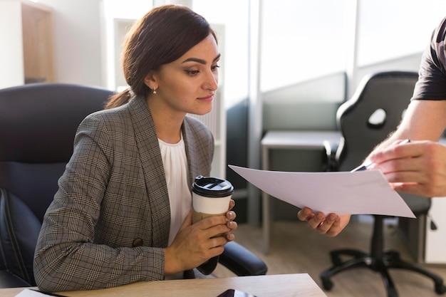 Imprenditrice guardando i documenti in ufficio Foto Gratuite