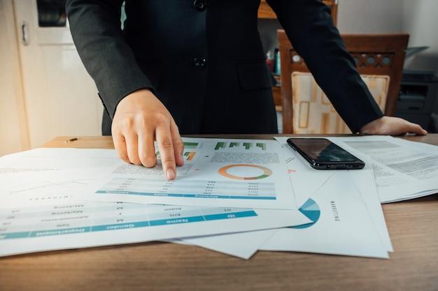 Предприниматель ищет оборот компании со многими документами на своем столе и указывая Premium Фотографии