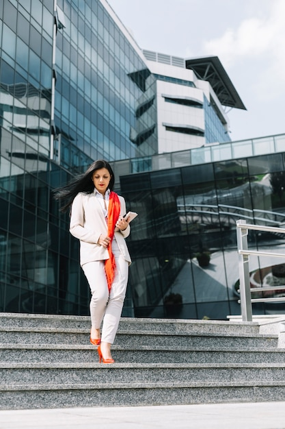 Businesswoman moving down staircase in front of building Free Photo