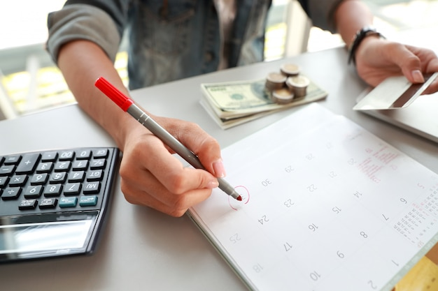 Businesswoman paying monthly and holding credit cards and writing on calendar Premium Photo