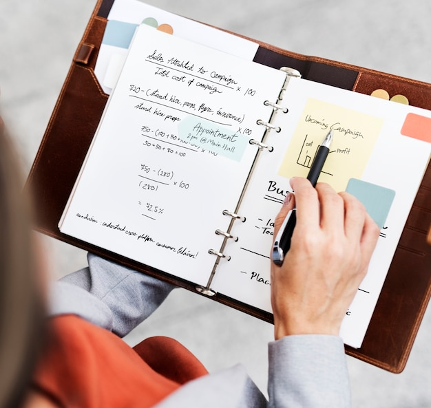 Businesswoman planning writing notebook marketing campaign concept Free Photo