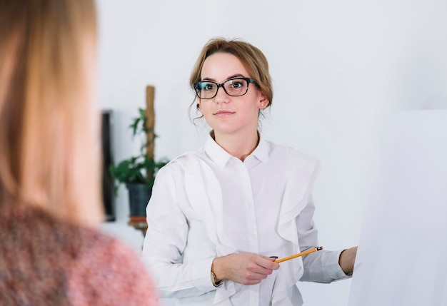 Businesswoman pointing at whiteboard while presenting her ideas to business partners Free Photo
