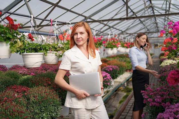 Деловая женщина позирует с ноутбуком, пока ее партнер обсуждает по телефону предложение в зеленом доме с цветами. Бесплатные Фотографии