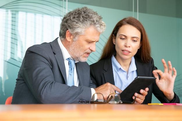 実業家が投資家にプロジェクトを提示します。詳細を説明するタブレット上のコンテンツを同僚に示す深刻な女性従業員。 無料写真