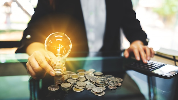 Businesswoman putting a light bulb over coins stack on the table while calculating for saving energy