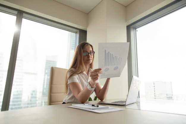 Businesswoman reading document with graphs Free Photo
