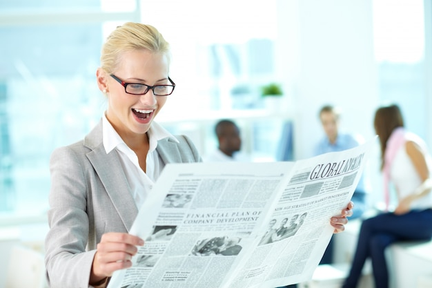 Businesswoman reading newspaper Free Photo
