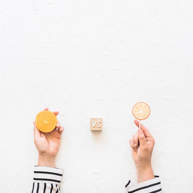 Businesswoman's hand holding citrus slice versus lollipop over white background Free Photo