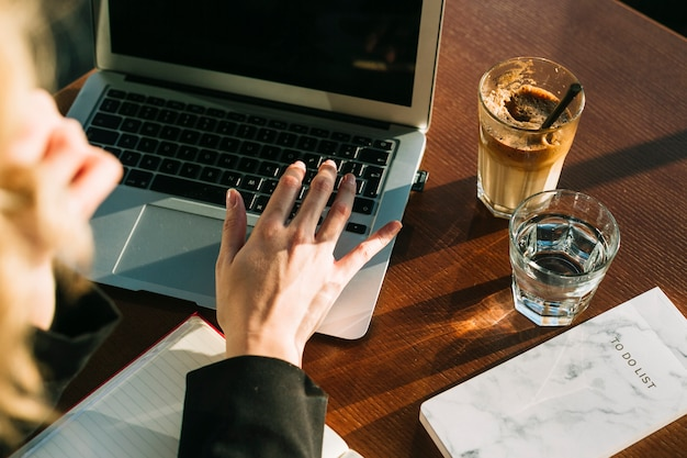 Businesswoman's hand working on laptop with glass of chocolate milkshake and water on wooden desk Free Photo