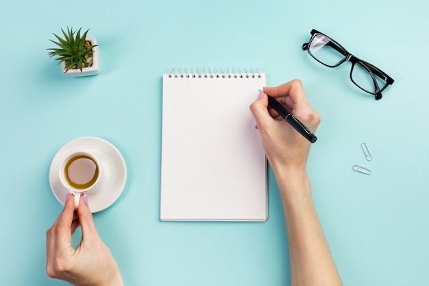 Businesswoman's hand writing on notepad with pen and holding coffee cup over the office desk Free Photo