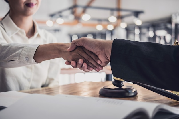 Businesswoman shaking hands with professional male lawyer after discussing good deal of contract in courtroom Premium Photo