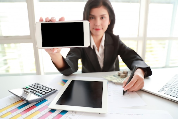 Businesswoman showing blank screen cell phone with tablet on table Premium Photo