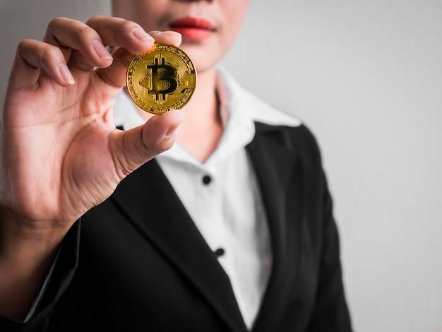 Businesswoman showing gold bitcoin. Premium Photo