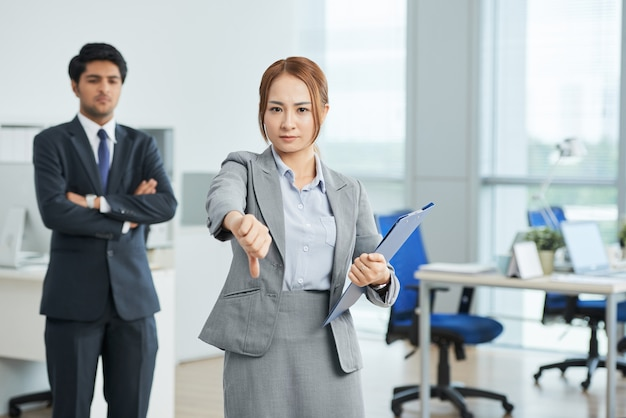 Businesswoman showing thumb down gesture, and man in suit with crossed arms Free Photo