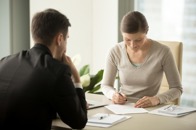 Businesswoman signing contract with businessman Free Photo