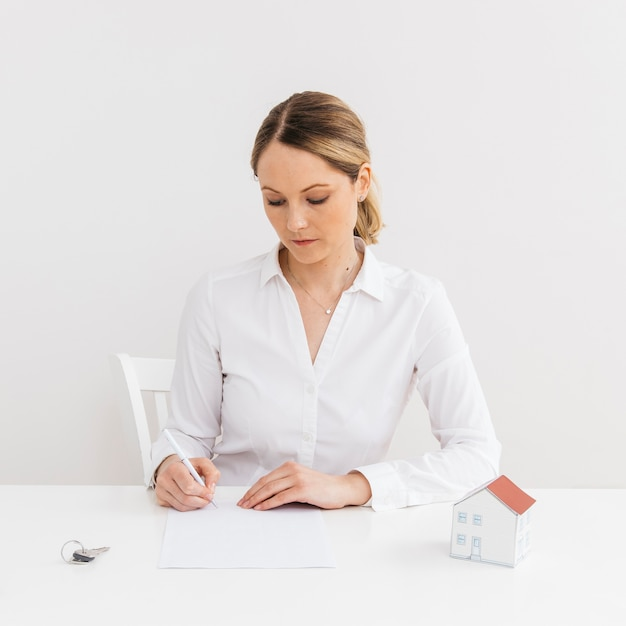 Businesswoman signing the document contract of a sale for a new house Free Photo